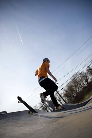 halfpipe: Portrait of a young skateboarder falling off of his board on a ramp at the skate park.