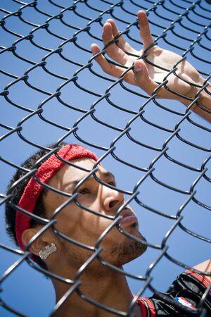 chainlinked: Deze jonge basketballer leunt tegen een keten verbonden hek op het basketbalveld.