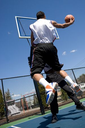 A young basketball player driving to the hoop with some fancy moves during a one on one game at the park. photo