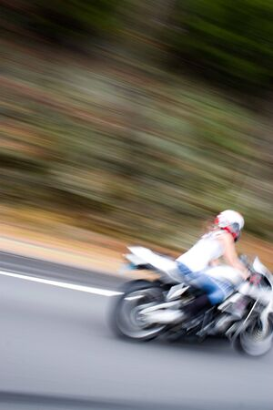 wife beater: Abstract blur of a pretty girl driving a motorcycle at highway speeds.  Intentional motion blur.