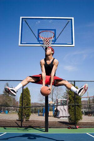 일부 멋진 동작으로 농구 대를 운전하는 젊은 농구 선수. 스톡 콘텐츠