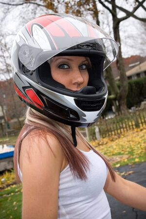 hot chick: A pretty blonde girl wearing a motorcycle helmet.