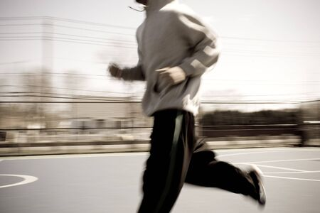 Abstract blur of a young man warming up by jogging at the basketball court.  Intentional motion blur.
