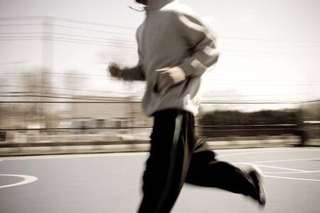 sudadera: Resumen borroso de un joven por el calentamiento de trotar en la cancha de baloncesto. Motion Blur intencional.