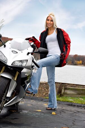 A pretty blonde posing with her motorcycle and riding gear. photo