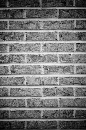 Bakstenen muur achtergrond in zwart en wit met vignettering.