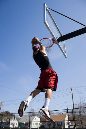 A young basketball player driving to the hoop for a slam dunk.