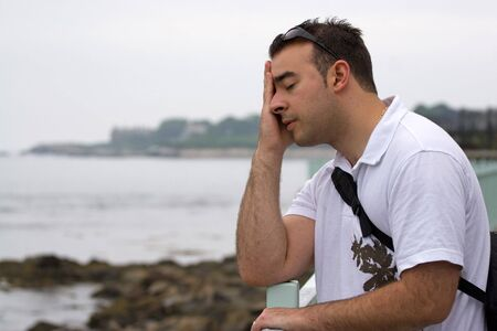 A young looking very upset in a natural setting by the sea. Stock Photo