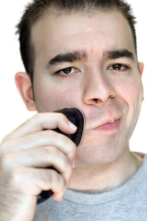 A closeup of a young man shaving his beard off with an electric shaver. photo