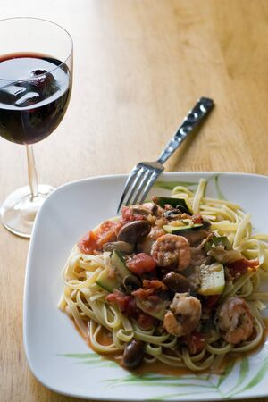 A delicious shrimp and pasta dish along with a glass of red wine. photo