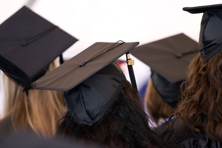 mortar hat: A group of college or high school graduates wearing the traditional cap and gown.  Shallow depth of field.