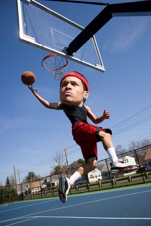 A basketball player with a large head driving to the hoop with some fancy moves. photo