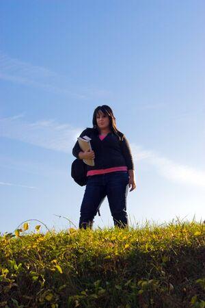 alumnos en clase: Una mujer joven caminando en el campus en un buen día con sus libros y mochila.
