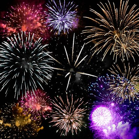 Beautiful fireworks exploding over a dark night sky in a grand finale display.  Very high resolution. Stock fotó