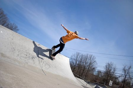 halfpipe: Portrait of a young skateboarder skating on a ramp at the skate park.
