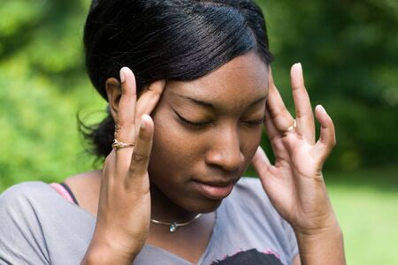 splitting headache: This young woman is experiencing intense stress or pain from a splitting headache. Stock Photo