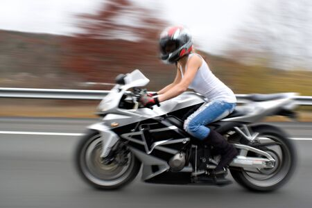 woman motorcycle: Abstract blur of a pretty girl driving a motorcycle at highway speeds.  Intentional motion blur.
