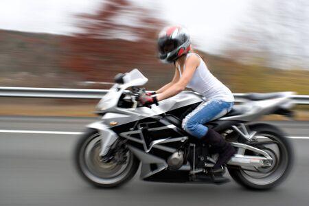 motorrad frau: Abstract Unsch�rfe von einem h�bschen M�dchen beim Fahren eines Motorrads auf der Autobahn Geschwindigkeiten. Vors�tzliche Bewegungsunsch�rfe.