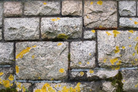 An old stone wall texture that is weathered and covered with some light moss. photo