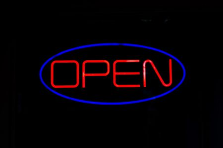 A neon OPEN sign isolated over black. photo