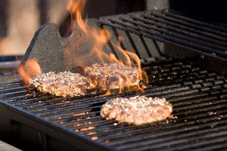 barbecuing: A closeup of some fresh and juicy hamburgers cooking on the grill.