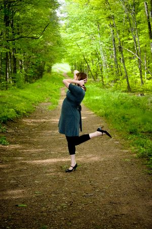 wooded path: A young woman posing on a wooded path.