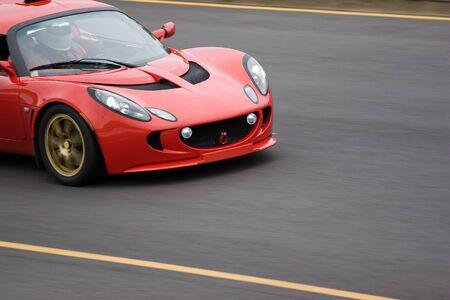 speeder: A red sports car speeding down the road.