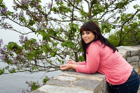 An attractive woman leans up against the wall along the historic Newport coast along the cliff walk . photo