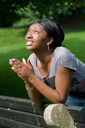 praying together: A young woman praying with her hands together. Stock Photo