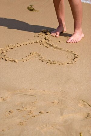 A young woman stands on the sandy shore by the heart she drew in the sand. photo