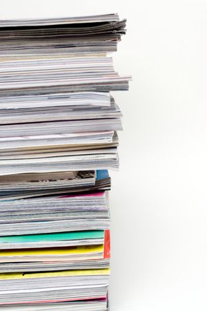 A large stack of magazines piled high.  Isolated over white with copyspace. photo