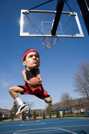 large ball: A basketball player with a large head driving to the hoop with some fancy moves. Stock Photo