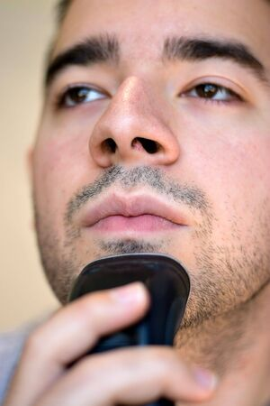 A closeup of a young man shaving his beard off with an electric shaver. Shallow depth of field. photo