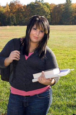 A young woman walking on campus on a nice day with her books and backpack.