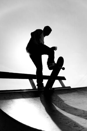 Silhouette of a young skateboarder at the top of the ramp. photo