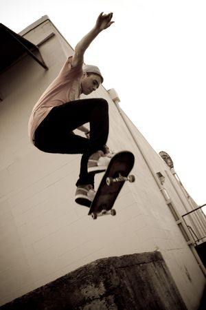skateboarding: A young skateboarder launches off a concrete loading dock in an urban setting.