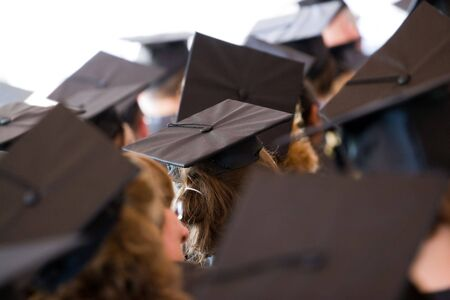 A group of college or high school graduates wearing the traditional cap and gown.  Shallow depth of field.