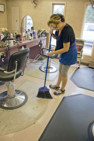 A hairdresser working in the salon sweeps up after her last client. Stock Photo - 5343584