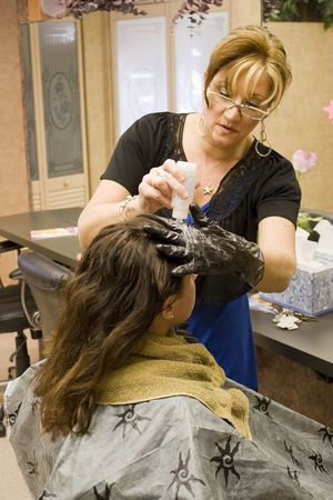 A hairdresser working on a clients hair color at the salon. photo