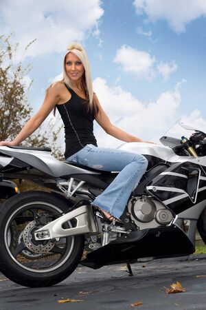 A pretty blonde woman seated on a motorcycle outdoors. Stock Photo