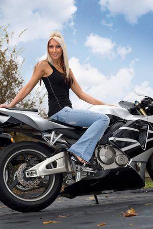 Une jolie femme blonde assise sur une moto en plein air. Banque d'images - 5343599