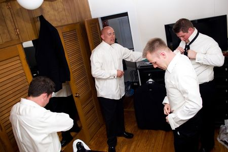 A groom along with his three groomsmen getting dressed and ready for the wedding. Stock Photo