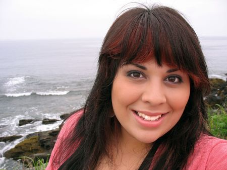 highlighted hair: A young hispanic woman with red highlights in her hair by the sea shore in Newport Rhode Island.