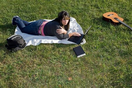 A young woman laying in the grass and using her laptop computer.  She could be a college student or even a musician. photo