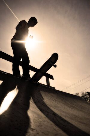 on ramp: Silhouette of a young skateboarder at the top of the ramp. Stock Photo