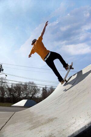 ni�o en patines: Retrato de un joven skater de patinaje por una rampa en el parque de patinaje. Foto de archivo