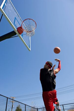 A young basketball player shooting in a hook shot or lay up. Stock Photo - 5469383