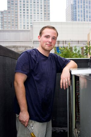 A young HVAC technician working on a rooftop. Stock Photo - 5480197