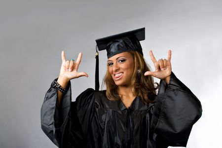 recent: A recent graduate posing in her cap and gown isolated over a silver background.