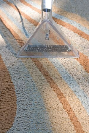 areas: A carpet cleaner in action on a contemporary rug. Stock Photo